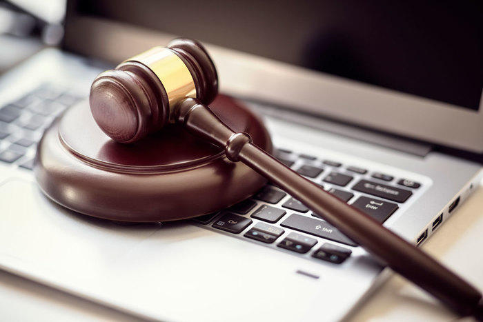 Gavel on top of laptop keyboard